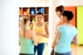 pregnancy, sport, fitness, people and healthy lifestyle concept - group of happy pregnant women talking in gym