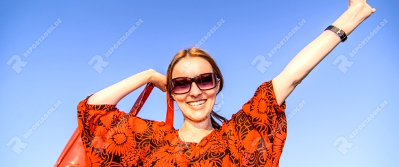 Young beautiful woman with red bag standing.