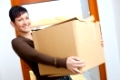 Woman lifting cardboard box while moving home, smiling.