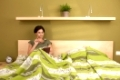 Woman reading book, holding glasses, sitting alone in double bed.