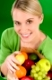 Healthy lifestyle - woman with fruit shopping paper bag on green background
