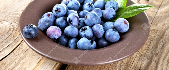 Fresh blueberries in bowl with leaves on wooden background