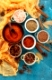 Dry colorful spices and condiments anise, paprika, saffron, pepper, salt, bay leaf, cinnamon in small bowls on blue background