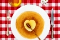 Pancakes heart with honeyflower and cutlery, top view