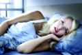 Worried young woman laying in bed sleepless at night