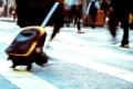 Blurred image of pedestrian with travel bag walking on crossroad at city street. Hong Kong. Art toning abstract urban background