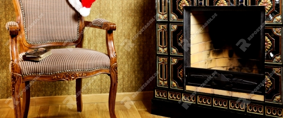 Old Antiques Armchair With Santa's Hat Near The Fireplace