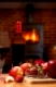 Red wine in bottle and glass with apple and strawberries on wooden table in front of roaring fire inside wood burning stove in brick fireplace