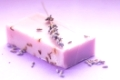 Soap with dry lavender over lilac background
