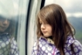Sad beautiful little girl leaning against a window standing thinking with downcast eyes reflected in the glass