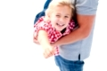 Close-up of little girl enjoying piggyback ride with her father against a white background