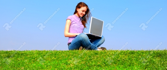 Girl with notebook sitting on grass against sky