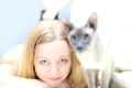 beautiful blond girl playing with cat in a bed