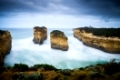 Loch Ard Gorge at Great Ocean Road. This long-exposure captures the movement of waves and clouds around the beautiful landmark of orange rocks