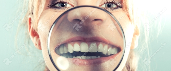 Happy young woman showing white teeth through magnifying glass.