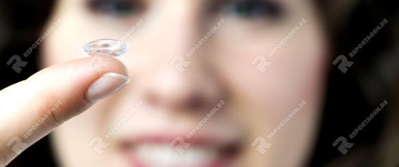 Closeup of a face of a woman with a contact lense on her finger