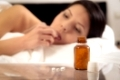 Woman suffering from illness or insomnia lying in bed about to take a tablet and a displayed bottle of medication on the nightstand, selective focus on the tablet bottle