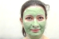 Young woman applying green algae facial mask.