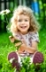 Happy smiling child with flower sitting on green grass outdoors in spring garden