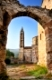 Image shows an old historic church in the town of Kardamili, southern Greece, framed by an old arch