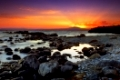 Image shows a spectacular sunset over a rocky seascape, in Mani peninsula, southern Greece