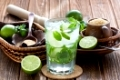 Mojito cocktail delicious summer drink with lime, mint and ice on rustic wooden background