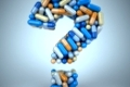 Pills or capsules as a question mark on blue background 3d